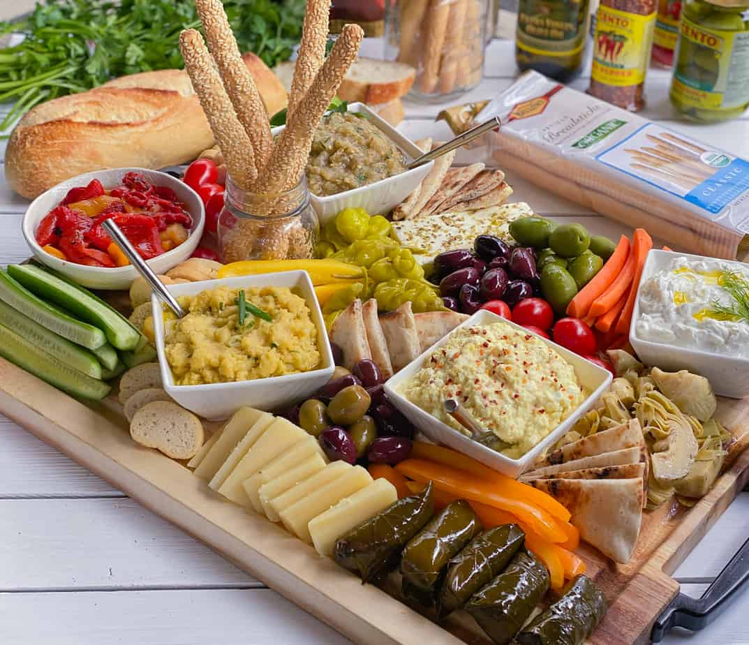 Large Greek appetizer platter with dolmades, pita bread, dips, veggies and olives.