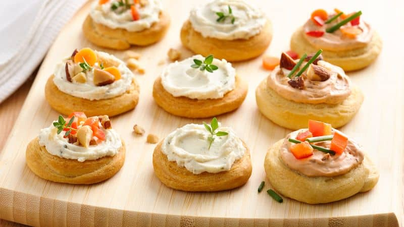 creamy cheese spread on crescent rounds on a board
