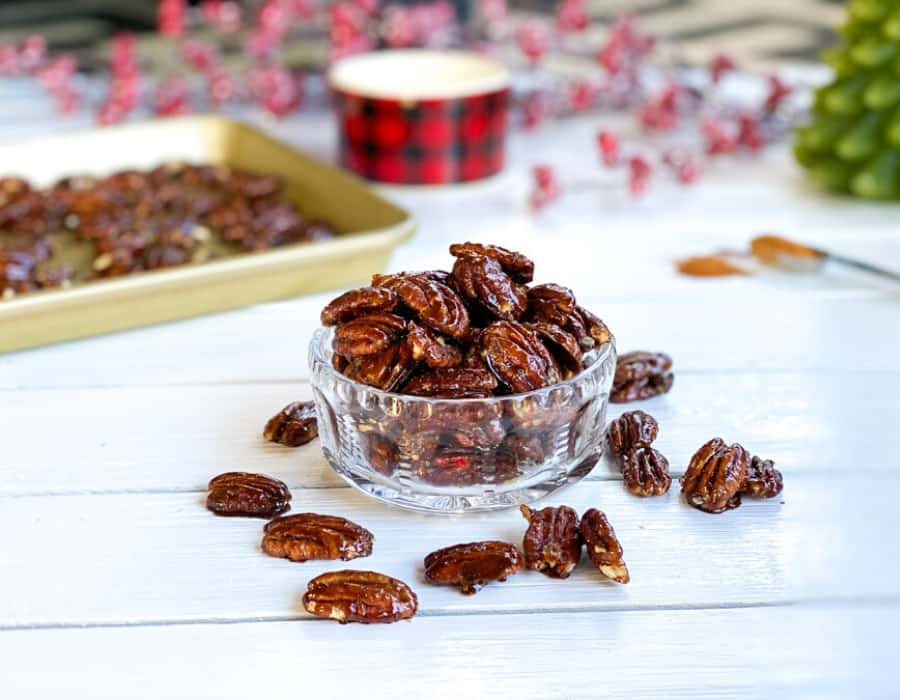 glazed holiday spiced pecans in a clear glass bowl
