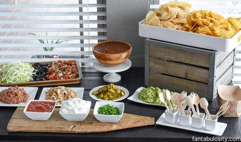 nacho bar set up with dips and chips for graduation party.