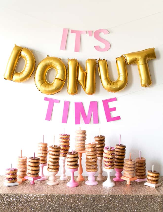 donut bar with skewered donuts on a table for graduation party.