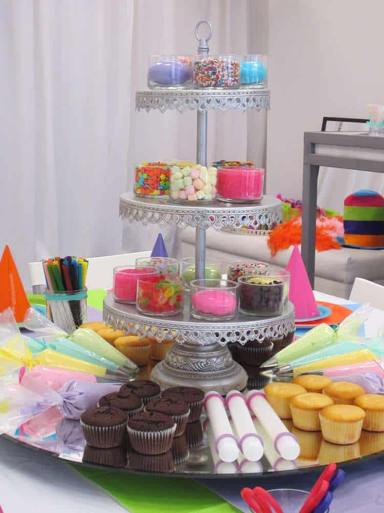 a 3 tiered stand with different cupcake toppings and cupcakes