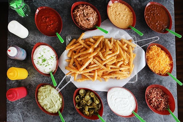 french fry bar with different toppings in bowls for graduation party.