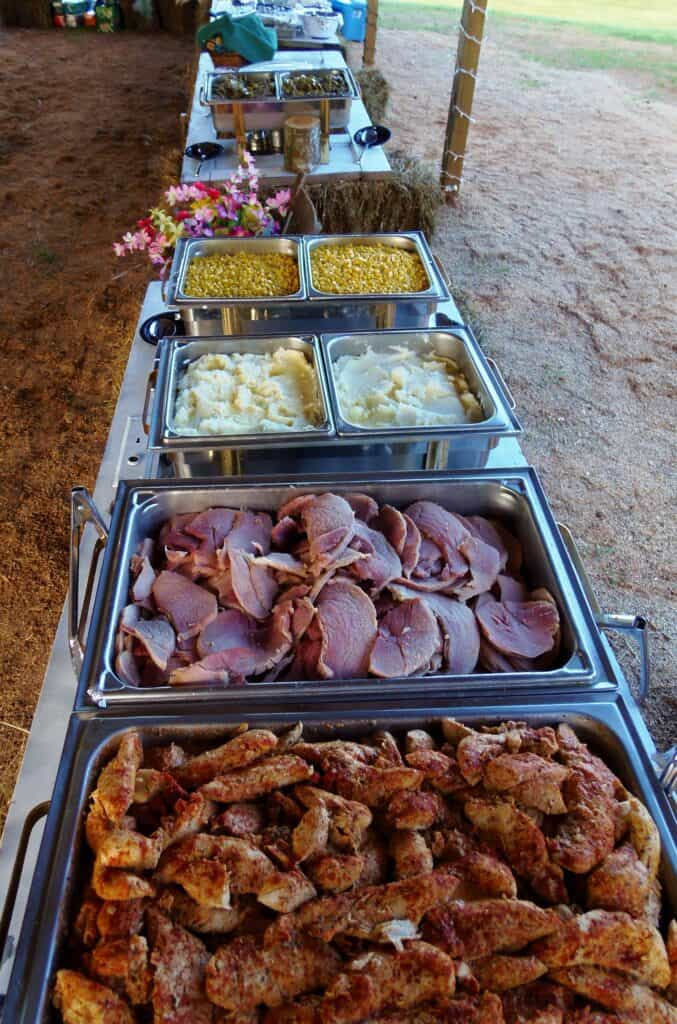 a traditional outdoor buffet set up with corn, mashed potatoes ham and greens