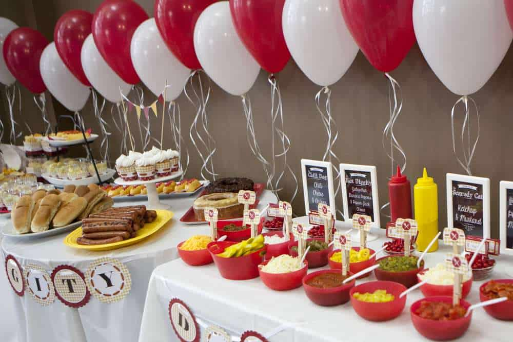 hot dog bar with white and red balloons and multiple toppings in bowls.