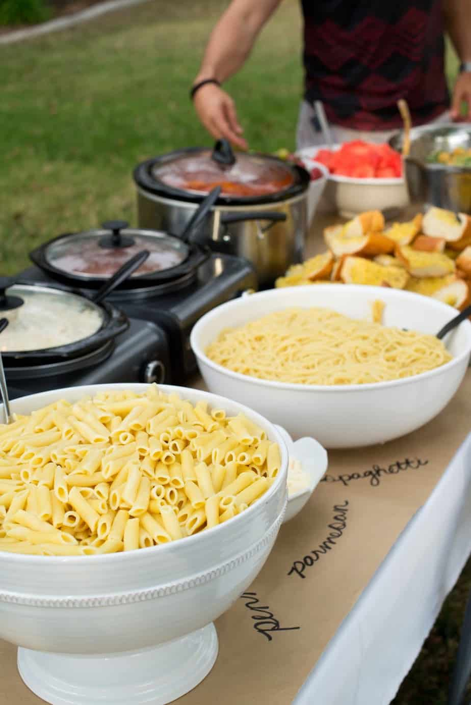 pasta buffet bar with different sauces in crock pots at graduation party.
