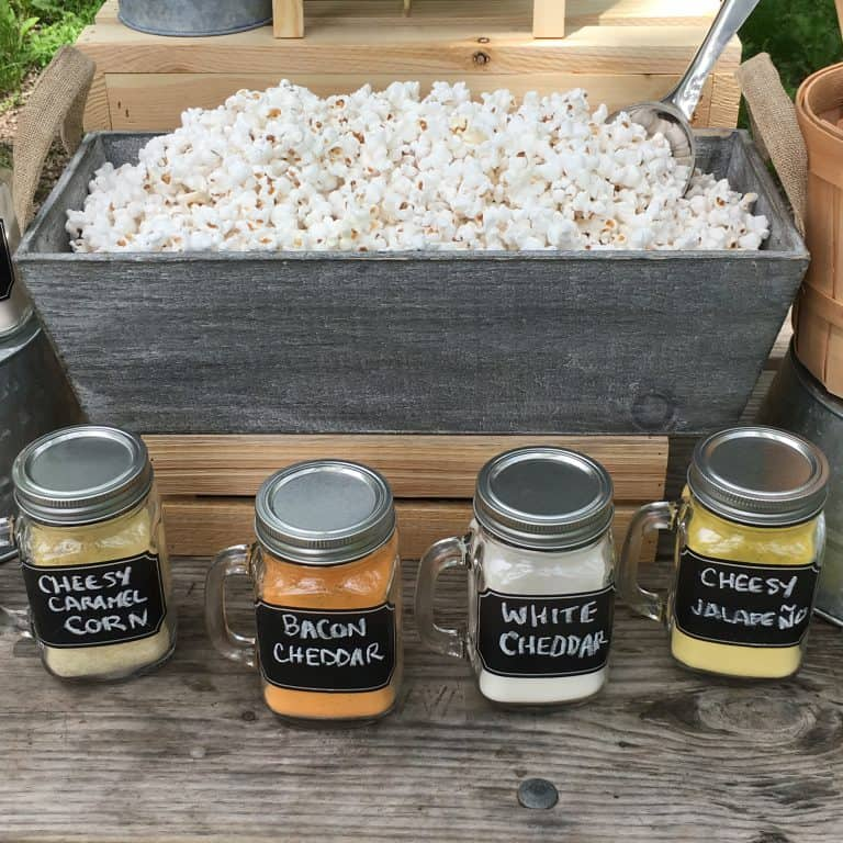 graduation popcorn bar setup with seasonings in mason jars.