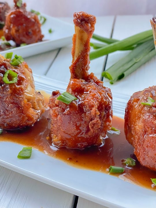 lollipop chicken wings standing upright on a white plate smothered in sauce.