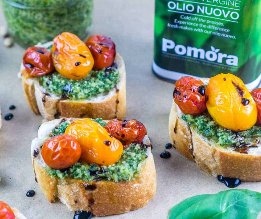easy pesto crostini appetizer with roasted tomatoes on top