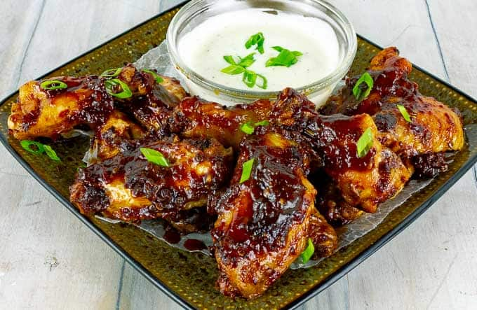 baked chicken wings appetizer smothers in bbq sauce on a plate