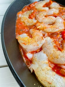 shrimp in a cast iron skillet with tomato sauce