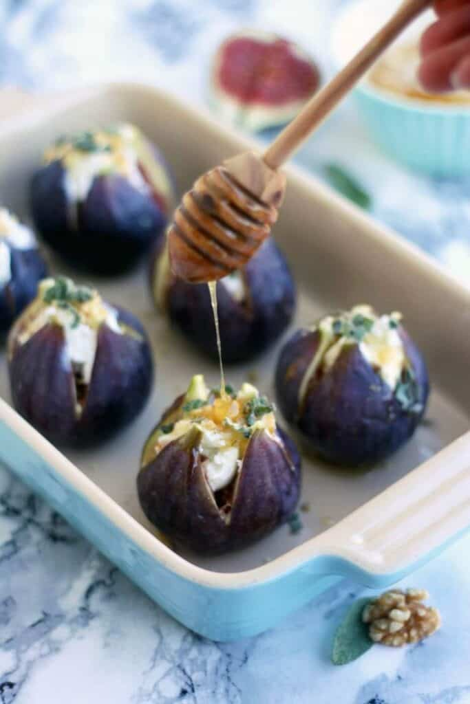baked figs appetizer stuffed with goat cheese in a dish drizzled with honey