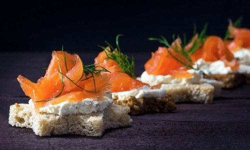 Bread cut into stars topped with cream cheese spread underneath raw salmon and dill.