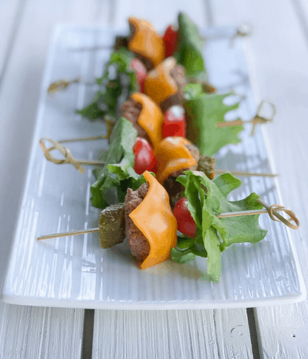 burger skewers appetizer on a long plate with melted cheese