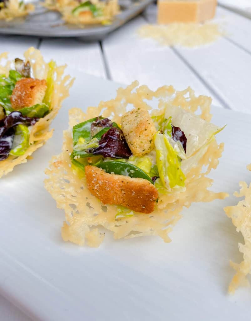 Parmesan cheese crisps filled with a caesar salad on a white plate.