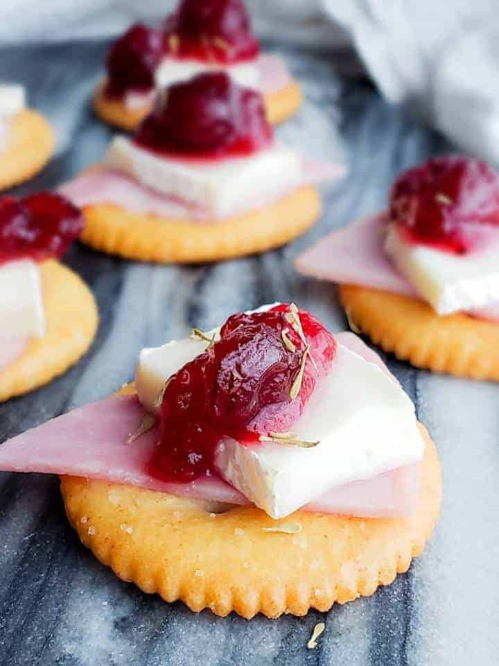 cranberry brie cracker appetizer with cranberry sauce on top