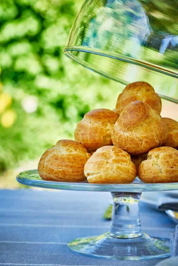 savory profiteroles appetizer stacked on a clear plate with a lid