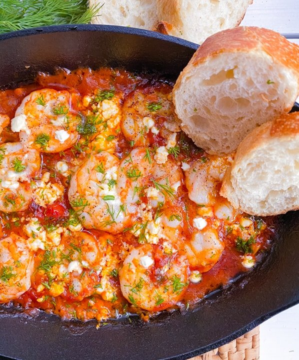 baked shrimp saganaki with feta cheese in a skillet with bread on the side