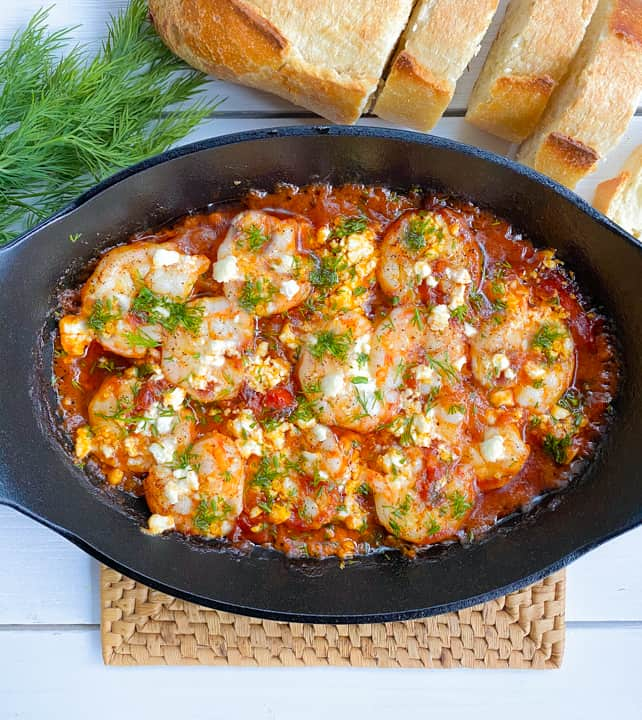 shrimp saganaki with feta cheese and tomatoes in a skillet