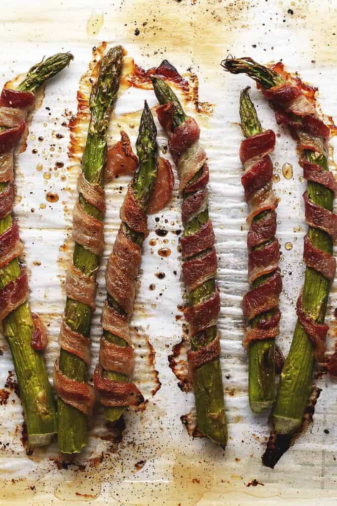 bacon wrapped asparagus appetizer on a baking sheet