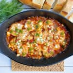 baked shrimp in skillet with tomato sauce and bread on the side