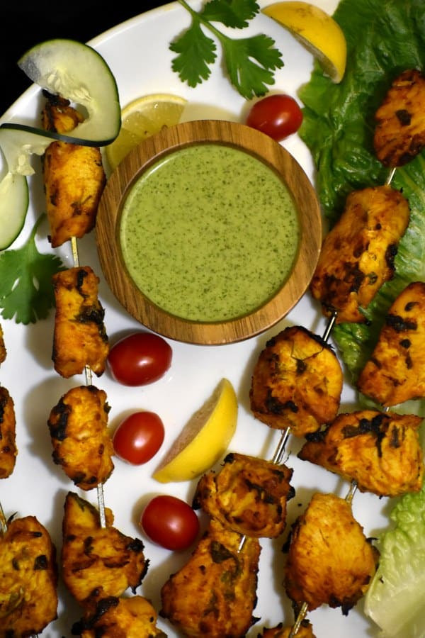 chicken tikkas skewers appetizer with dipping sauce on a plate