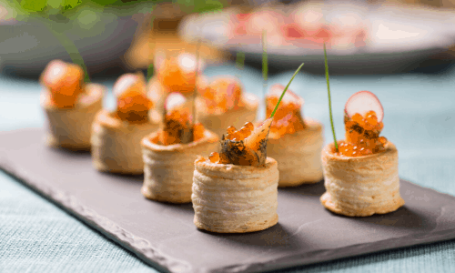 canapes on a slate being served at a party