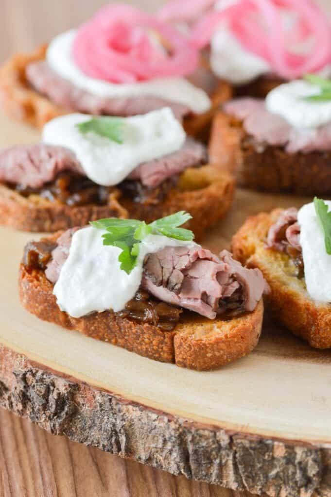 Roast Beef Crostini Hors d'oeuvres on a wooden plank