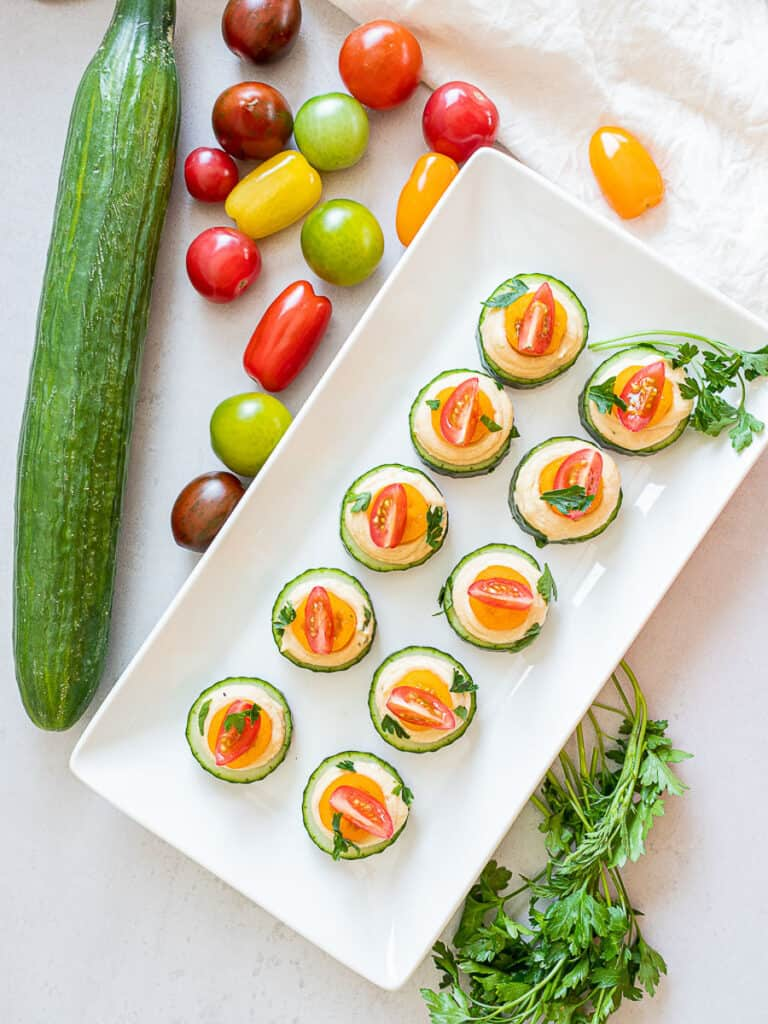 easy cold cucumber canapes on a plate with tomatoes on top