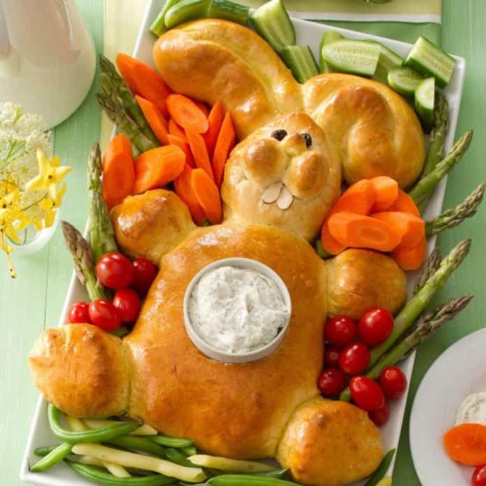 bread shaped into an Easter bunny surrounded by veggies.