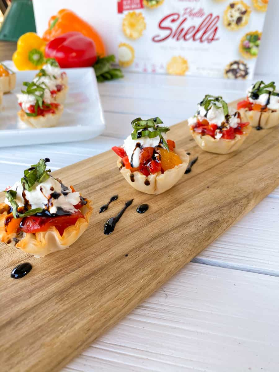 phyllo cups finger food stuffed with peppers and burrata cheese.