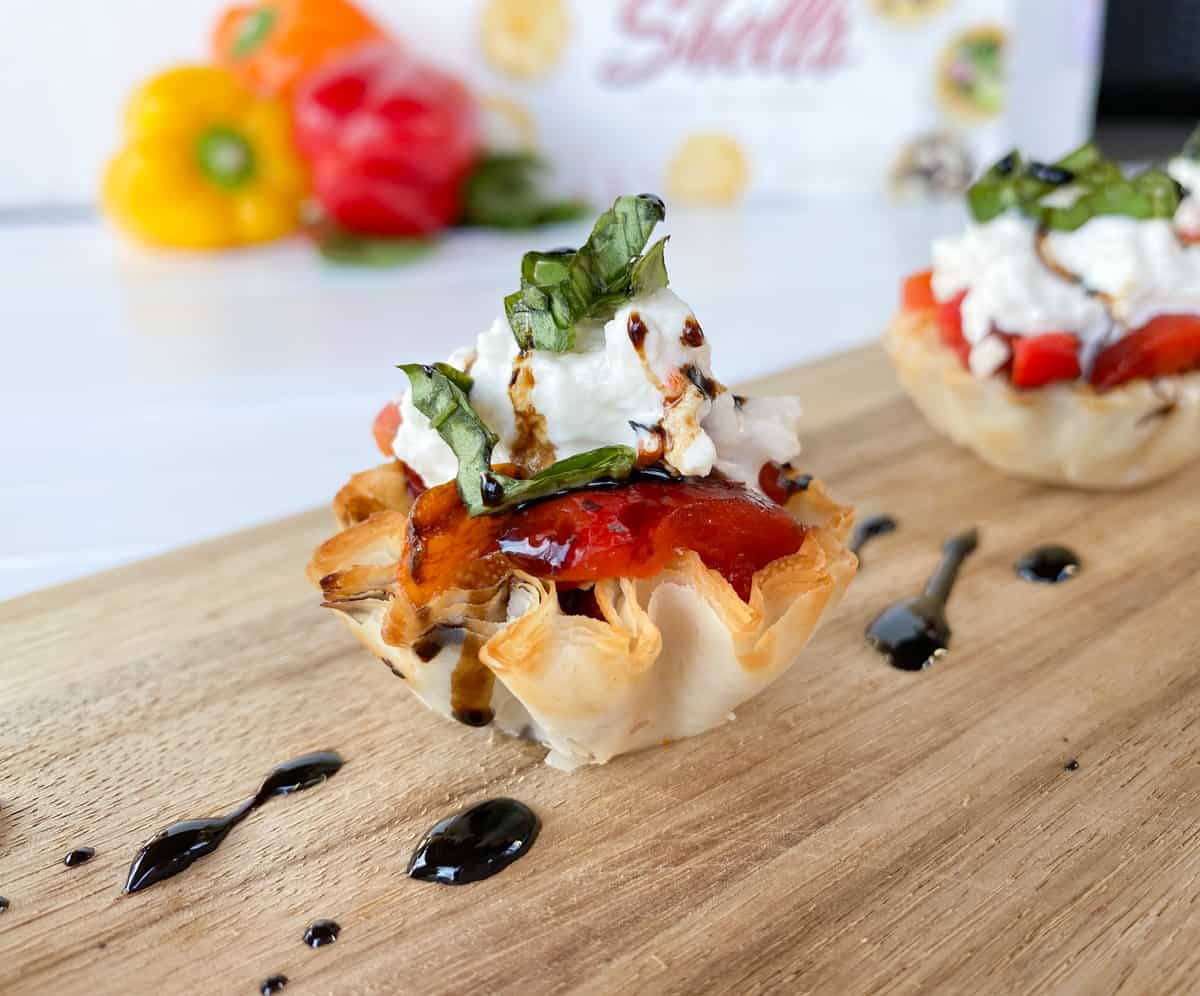 phyllo cups appetizer stuffed with peppers and burrata cheese on a board.