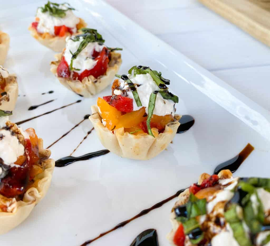 phyllo shells stuffed on a plate topped with balsamic vinegar