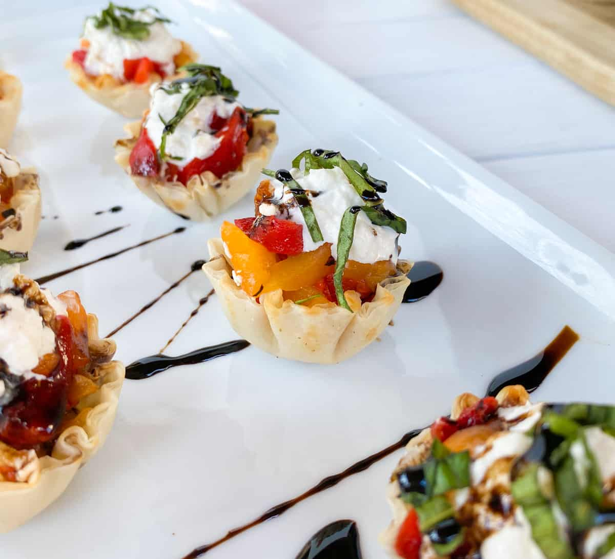 phyllo shells stuffed on a plate topped with balsamic vinegar.