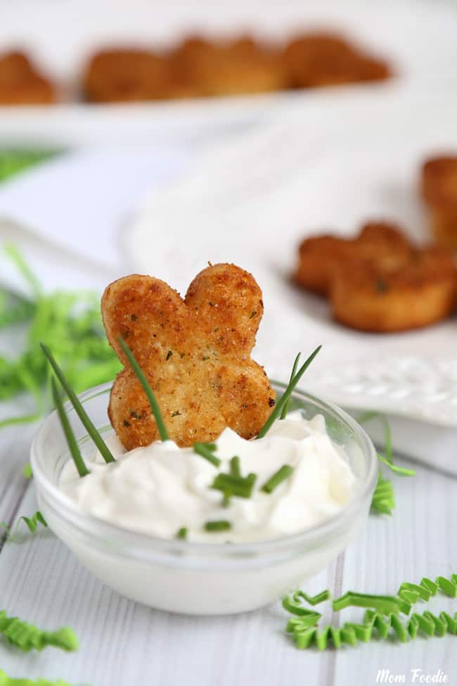 mini Easter bunny croquettes appetizer sitting in a bowl of sour cream.