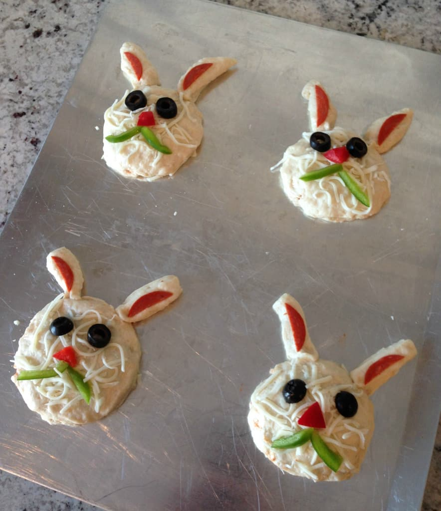 Easter bunny biscuit appetizers shaped into a head on a baking pan.