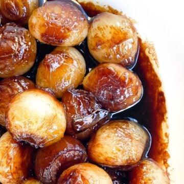 caramelized pearl onions in a bowl with balsamic glaze.