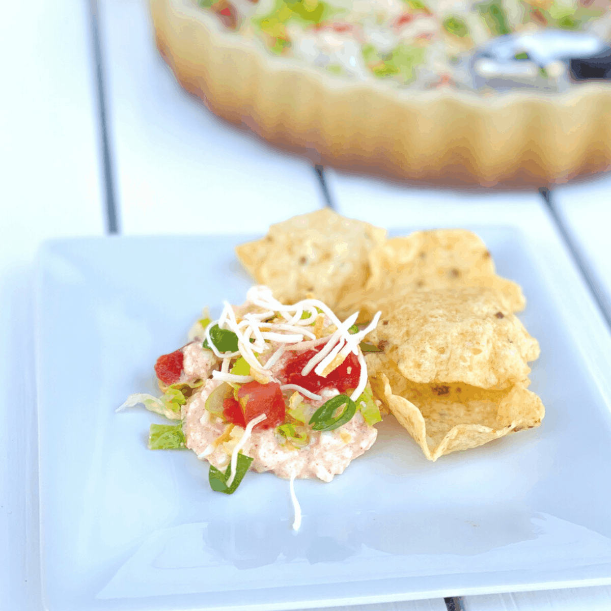 cottage cheese taco dip with tortilla chips on a plate