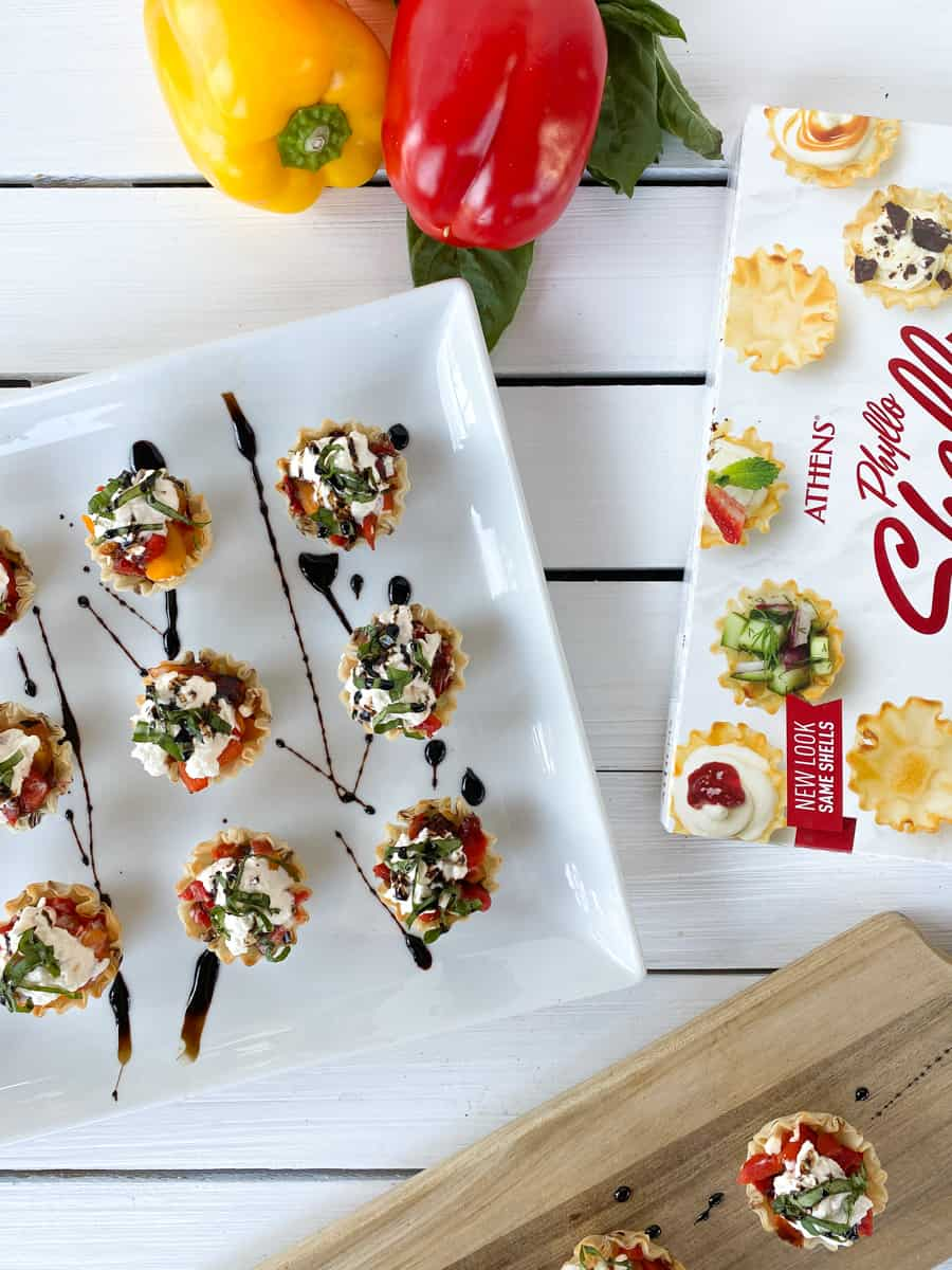 caprese phyllo cups with roasted peppers on a white plate.