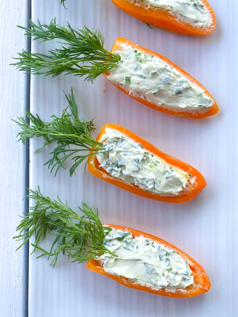 mini orange peppers stuffed with cream cheese and dill leaves to resemble a carrot