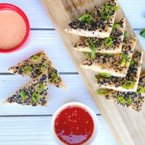 shrimp toast triangles on a table with sauces
