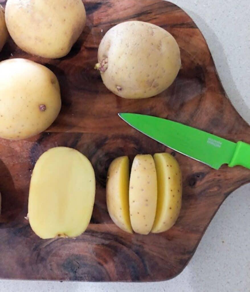 yukon gold potatoes cut into thirds on a cutting board
