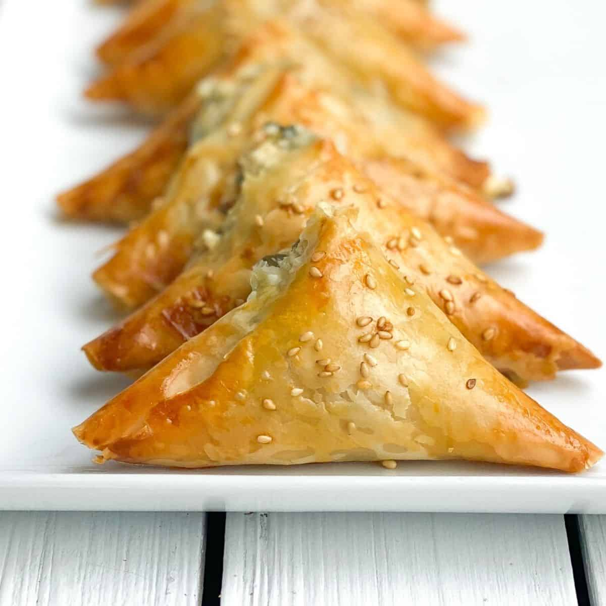 mini spanakopita pies on a white plate lined up.