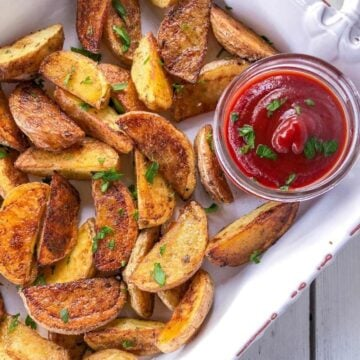 Crispy oven baked potato wedges in a white dish with ketchup.