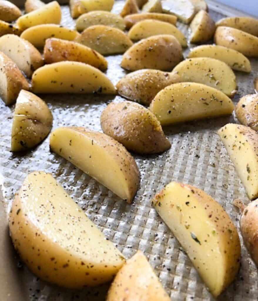seasoned potato wedges on a baking sheet