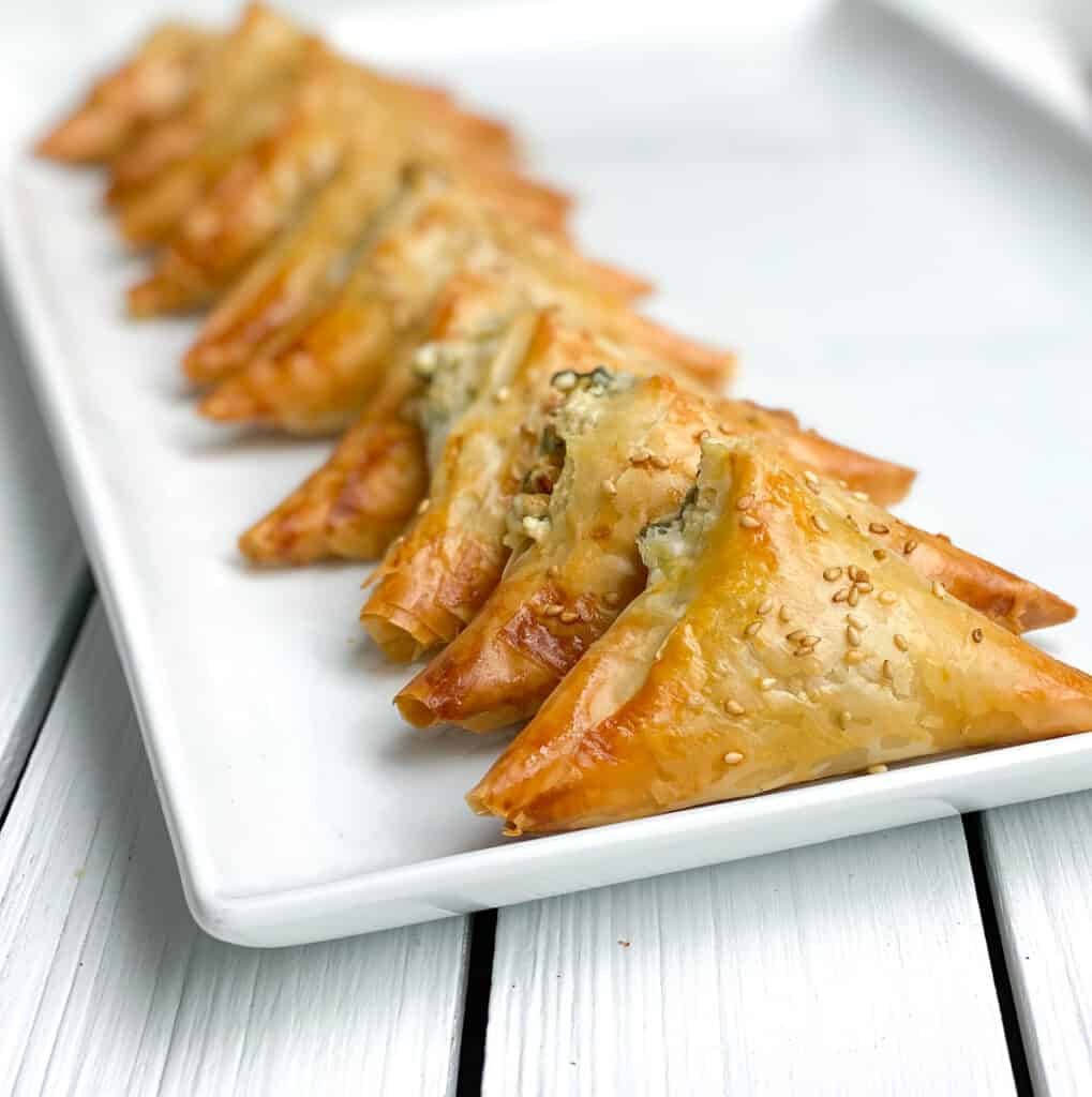 spinach and feta phyllo triangles appetizer on a white plate