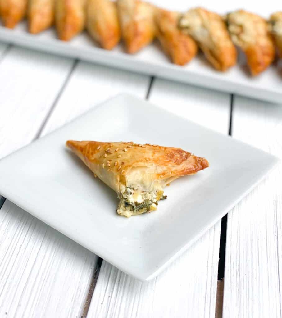 mini spinach triangle pie with feta cheese filling spilling out