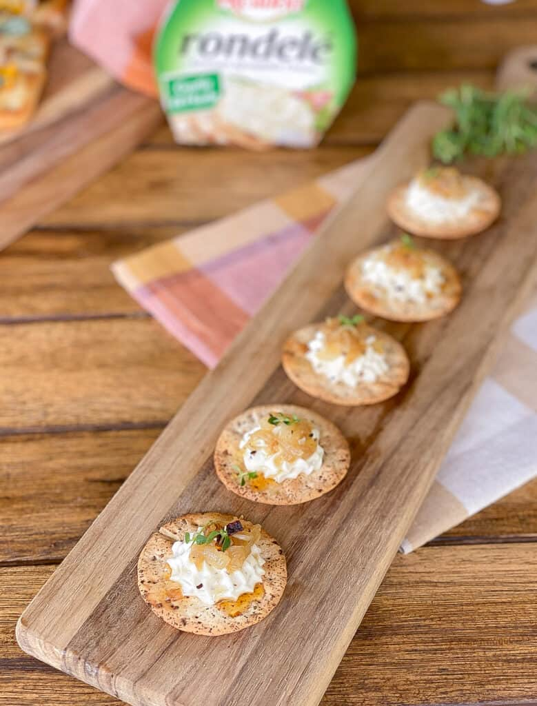 cheese and cracker canapes on wooden board