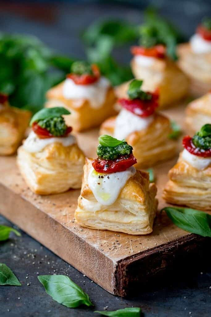 squares of puff pastry topped with cheese, tomato slice and pesto