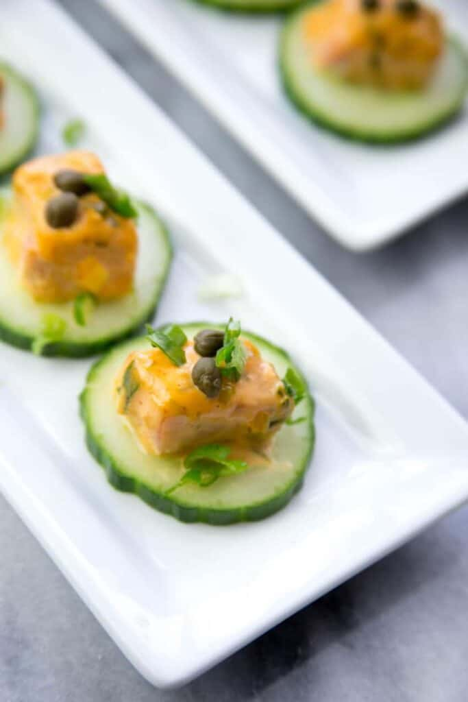 salmon on top of slices of cucumbers topped with capers